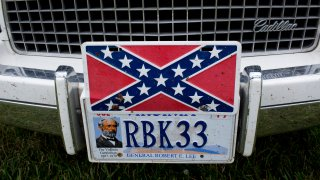 A confederate flag license plate is seen on a Cadillac.