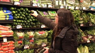 Woman picking produce in a grocery store