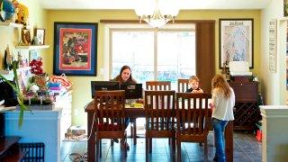 Kim Borton, left, works from home while her children Logan Borton, center, age 6, and Katie Borton, age 7, work on an art project in Beaverton, Ore.