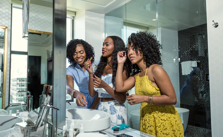 Three women look into bathroom mirror and get ready.