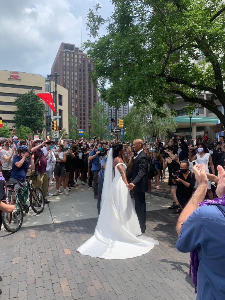 couple in tuxedo and wedding dress with protesters nearby