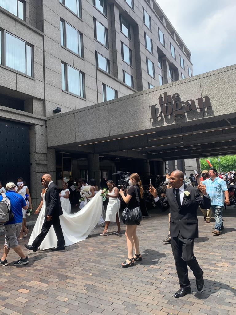 photographers and wedding party outside hotel, protesters with signs in background