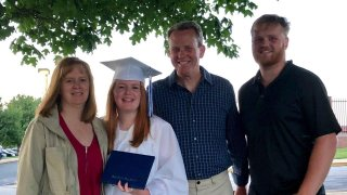family posing with girl in graduation cap and gown