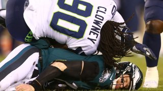 Quarterback Carson Wentz #11 of the Philadelphia Eagles is hit by Jadeveon Clowney #90 of the Seattle Seahawks during the NFC Wild Card Playoff game at Lincoln Financial Field