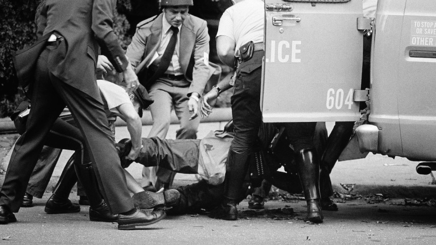 """Officers lift gunshot victim James Ramp into police van after he was shot during confrontation with radical group """"MOVE"""" Tuesday morning, August 8, 1978 in Philadelphia's west side."""