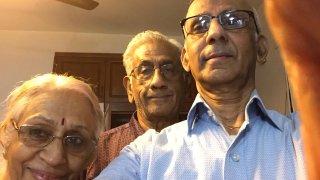 A woman and two men take a selfie