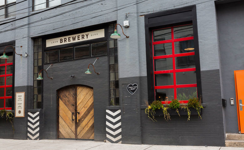 Exterior of Love City Brewing with grey brick facade and red-paned windows