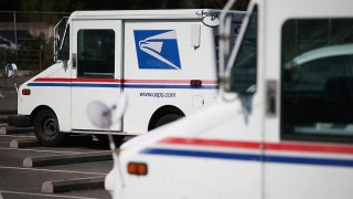 U.S. Postal Service mail vehicles sit in a parking lot at a mail distribution center