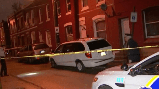A police cruiser and police tape surround a van in front of a home in North Philadelphia, where a man was shot.