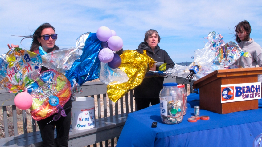 In this April 2, 2019, file photo, Lisa Cordova, left, Cindy Zipf, center and Alison McCarthy, right, of the Clean Ocean Action environmental group, unfurl a banner made of balloons they picked up from the beach at Sandy Hook N.J.