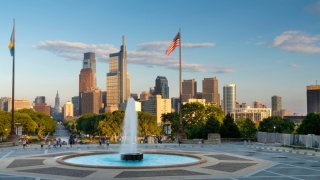 A fountain shoots water into the air as a pole with the American flag, as well as a row of skyscrapers, can be seen in the background of the Philadelphia skyline.