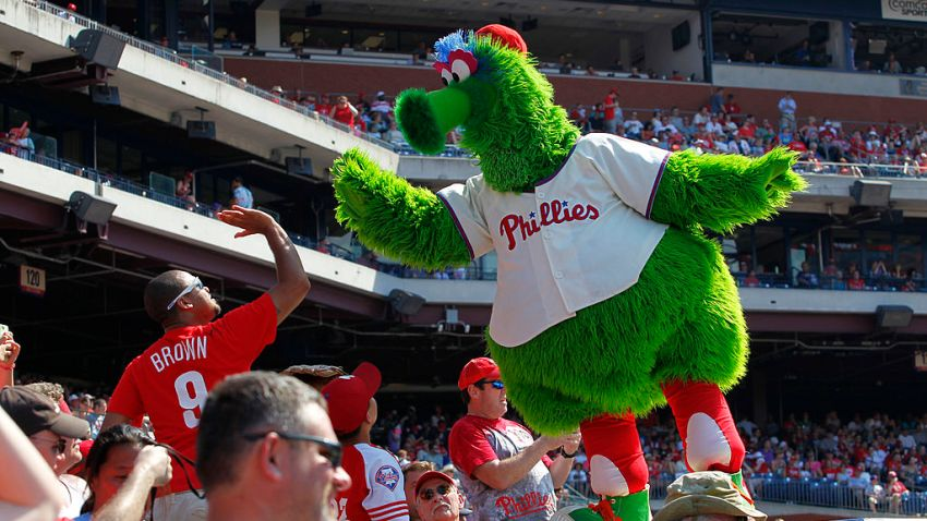 The Phillie Phanatic high-fives a fan during a game between the Philadelphia Phillies and the Atlanta Braves at Citizens Bank Park