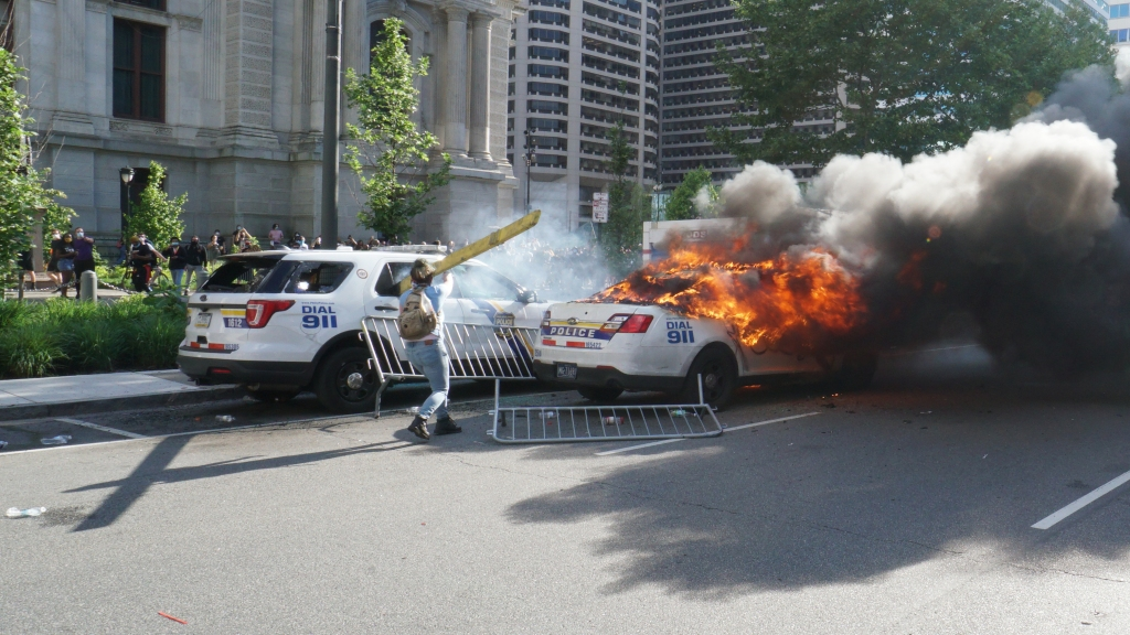 A woman is seen holding a piece of wood as a Philadelphia Police Department car burns in front of Philadelphia City Hall.