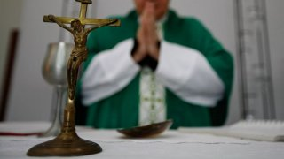 A crucifix sits on a table in front of a priest who is wearing a robe and has his hands clasped in prayer.