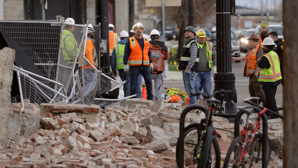 Construction workers look at the rubble from a building after an earthquake, March 18, 2020, in Salt Lake City. A 5.7-magnitude earthquake shook the city and many of its suburbs.