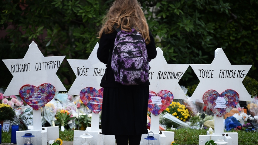 A woman stands at a memorial outside the Tree of Life synagogue
