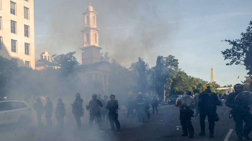 Tear gas floats in the air as a line of police move demonstrators away from St. John's Church across Lafayette Park from the White House, as they gather to protest the death of George Floyd, Monday, June 1, 2020, in Washington.