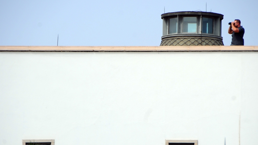 A man uses binoculars atop the United States embassy in Tunis, Wednesday, Sept. 12, 2012 as Muslims demonstrate outside the embassy to demand the closure of the embassy and the departure of the ambassador.