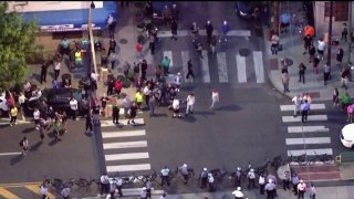 aerial image of crowd gathered outside police station. some in crowd have baseball bats