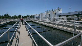 In this May 20, 2015, file photo, Michael Ruiz, shift superintendent for Wastewater Treatment II, at the Donald C. Tillman Water Reclamation Plant tours the Secondary Treatment Clarifiers tanks at the Los Angeles Sanitation plant where millions of gallons of wastewater are purified each day in Van Nuys, Calif.