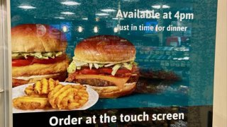A sign shows burgers and waffle fries from Wawa.