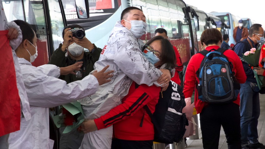 A medical worker from China's Jilin Province, in red, embraces a colleague at Wuhan Tianhe International Airport in central China's Hubei Province, Wednesday, April 8, 2020.