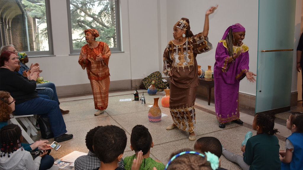 Women dancing in outfits from African culture in front of a crowd of children.