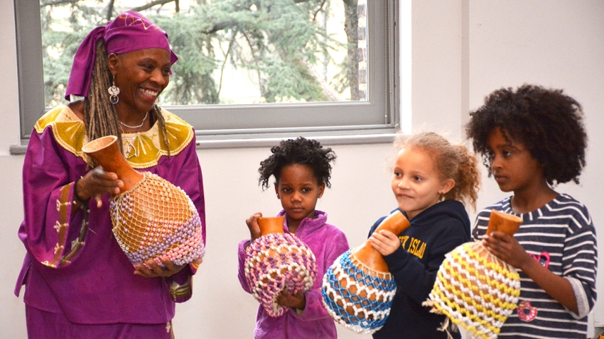 A woman and children play instruments from African culture.