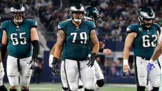 Philadelphia Eagles' Lane Johnson (65), Brandon Brooks and Jason Kelce (62) walk up to the line of scrimmage in the second half of an NFL football game against the Dallas Cowboys