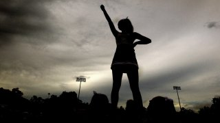 A cheerleader in silhouette