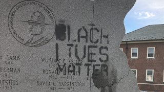 """The phrase """"Black Lives Matter"""" is painted on a Delaware State Police memorial."""