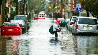A resident walks through flood water and past a stalled ambulance in the aftermath of superstorm Sandy on Tuesday, Oct. 30, 2012 in Hoboken, NJ.