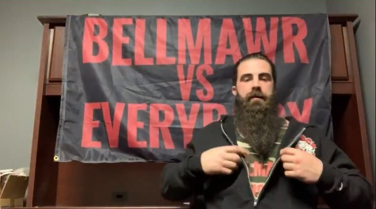 """Man sitting in front of flag reading """"Bellmawr versus Everybody"""""""