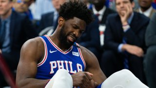 Philadelphia 76ers center Joel Embiid (21) reacts after falling on his injured hand during the third quarter against the Oklahoma City Thunder at Wells Fargo Center.