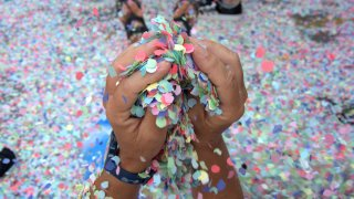 A par of hands holds confetti, with more on the ground, during a parade.