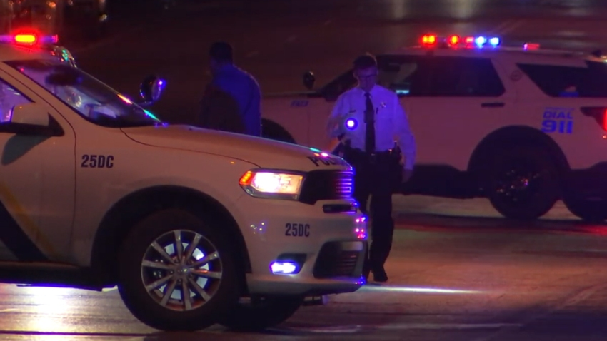 Philadelphia police officers stand behind highway patrol cruisers as they investigate a high-speed chase following a drive-by shooting in Philadelphia.