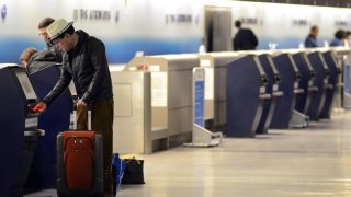 A man checks in his luggage at at kiosk at Philadelphia International Airport.