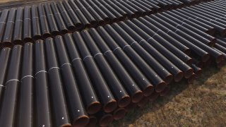 In this aerial view steel pipes lie stacked ahead of construction of a natural gas pipeline