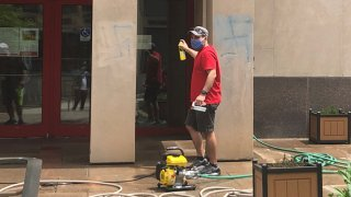 A man attempts to scrub away swastikas that were spray painted on an American Red Cross building in Philadelphia.