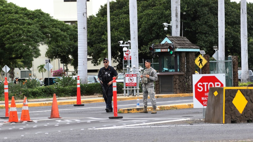 Security stand outside the main gate at Joint Base Pearl Harbor-Hickam, Wednesday, Dec. 4, 2019, in Hawaii. A shooting at Pearl Harbor naval shipyard in Hawaii left at least one person injured Wednesday, military and hospital officials said.