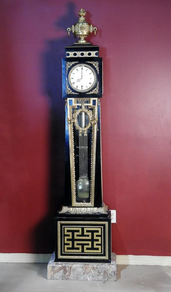 A black and bronze tower clock with a swinging pendulum and single weight. The case is ebonized with gilt bronze decoration, topped off by a massive finial. It all rests atop a thick marble plinth.
