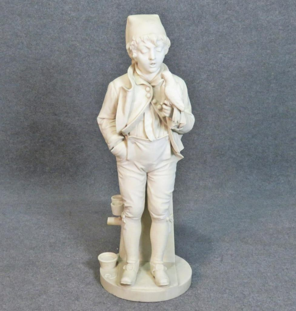 A carved, white marble sculpture of a boy holding a parrot. He leans against a pillar.