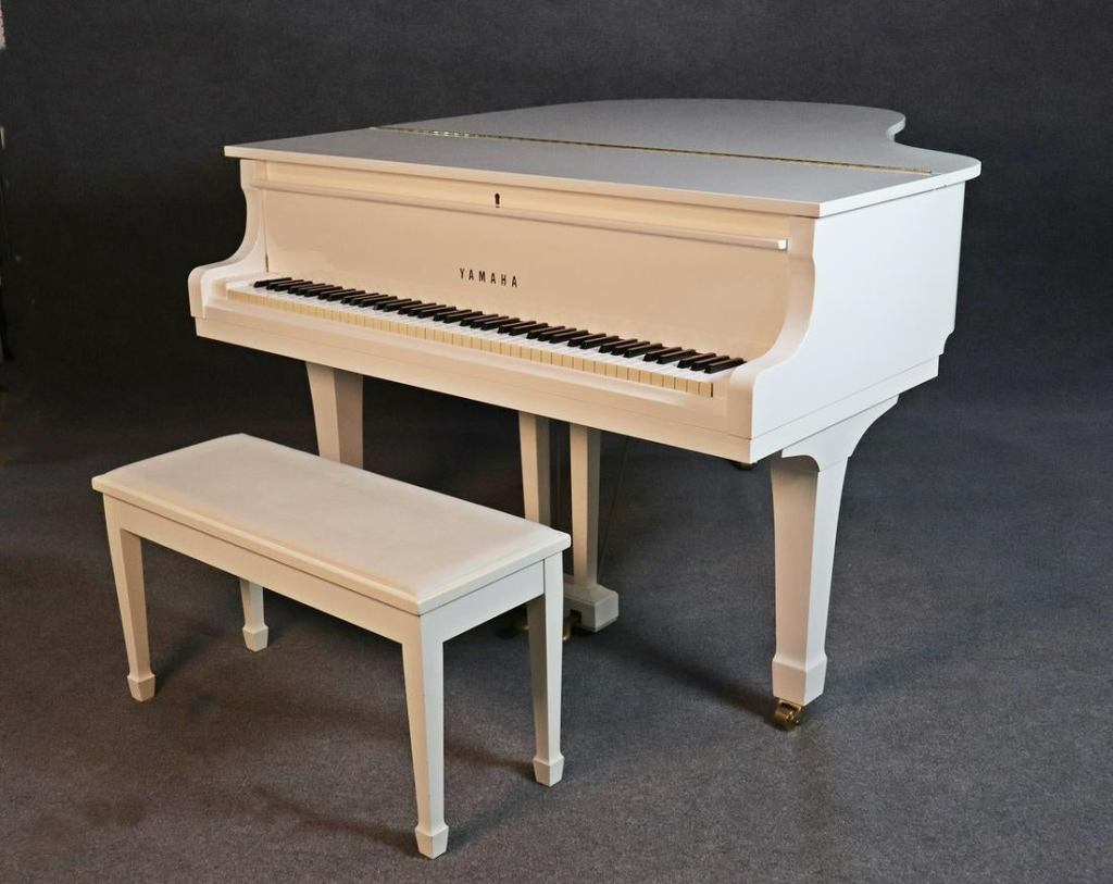 A white lacquered baby grand piano with a matching white bench. The piano has brass fittings and pedals.