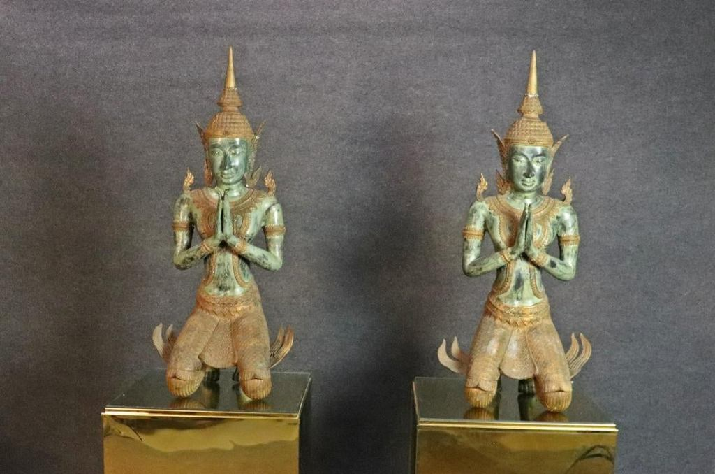 Two bronze Buddha statues with hands together, appearing to be praying.