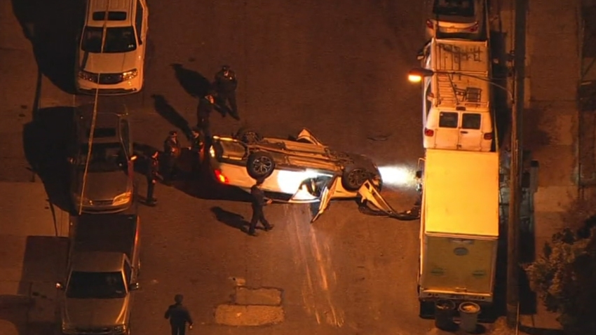 Police surround an overturned car after it crashed following a fatal shooting in Southwest Philadelphia.