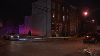 Philadelphia police officers use flashlights behind crime scene tape after a shooting.