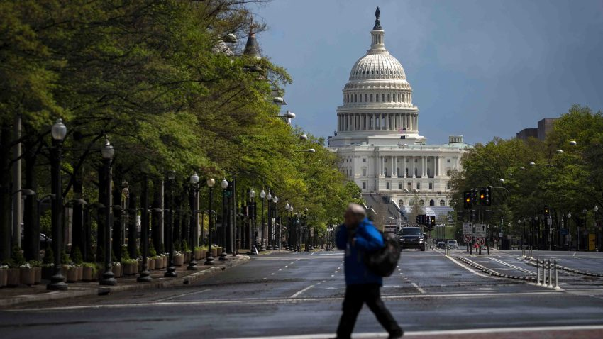 In this April 13, 2020, file photo, a pedestrian crosses a street past the U.S. Capitol in Washington, D.C.
