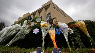 a makeshift memorial of flowers rests on bushes outside the Tree of Life Synagogue in Pittsburgh.