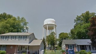 white water tower, trees and homes