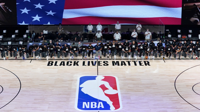 Members of the New Orleans Pelicans and Utah Jazz kneel together around the Black Lives Matter logo on the court during the national anthem before the start of an NBA basketball game Thursday, July 30, 2020, in Lake Buena Vista, Fla.